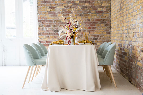 Styled wedding table with place settings, beeswax candles and flowers