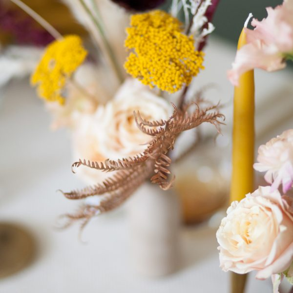 Close-up of flowers and beeswax candles on a wedding table