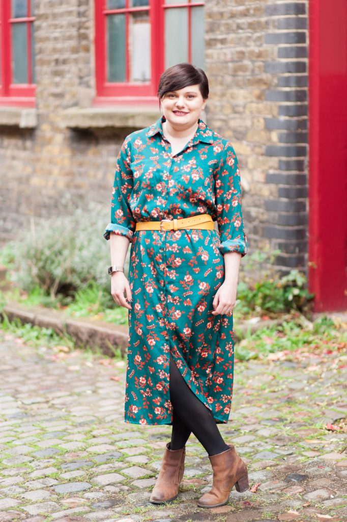 Wedding stylist, Catherine, stands on a cobbled street wearing a colourful dress and smiling at the camera.