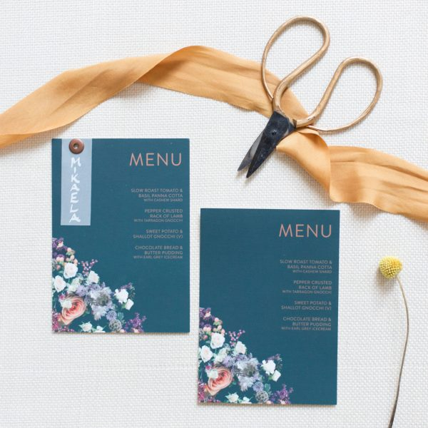 Flatlay of blue and copper menu cards with scissors and ribbon