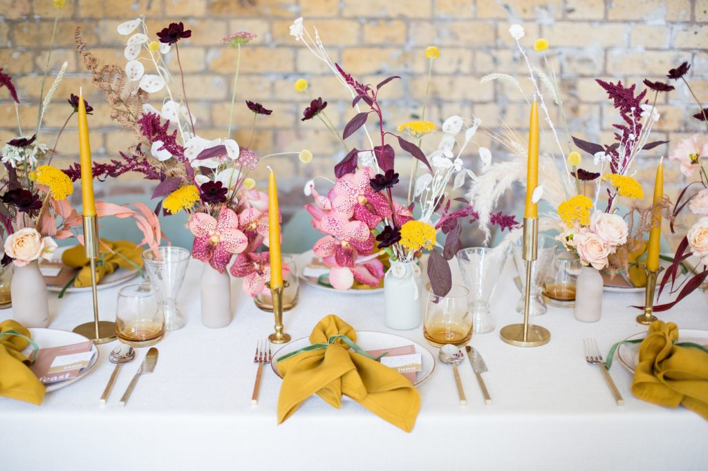 Wedding tablescape design on a long table with dried flowers and place settings