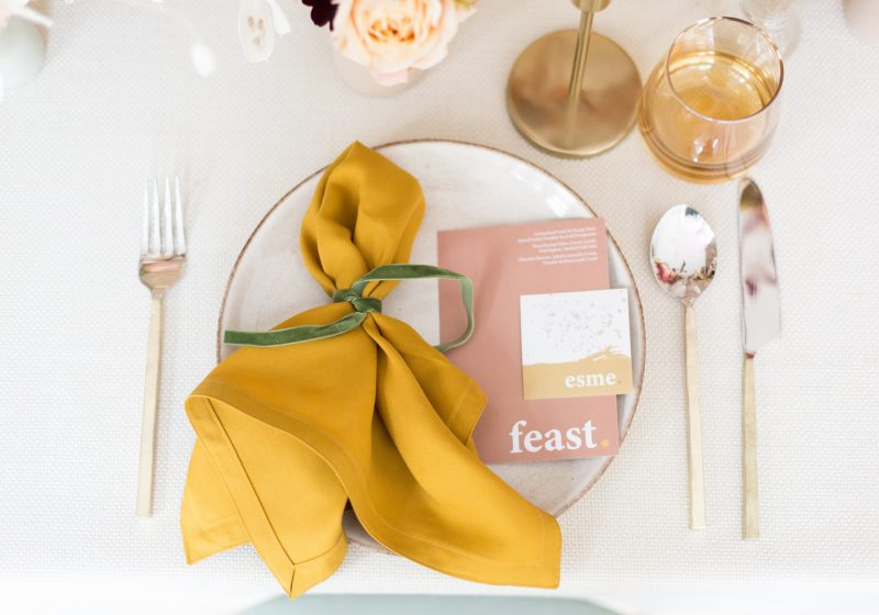 A styled place setting with menu card, napkin, cutlery and glassware