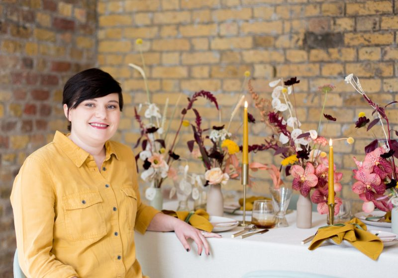Catherine, founder of All Things Considered, sitting in front of a styled wedding table