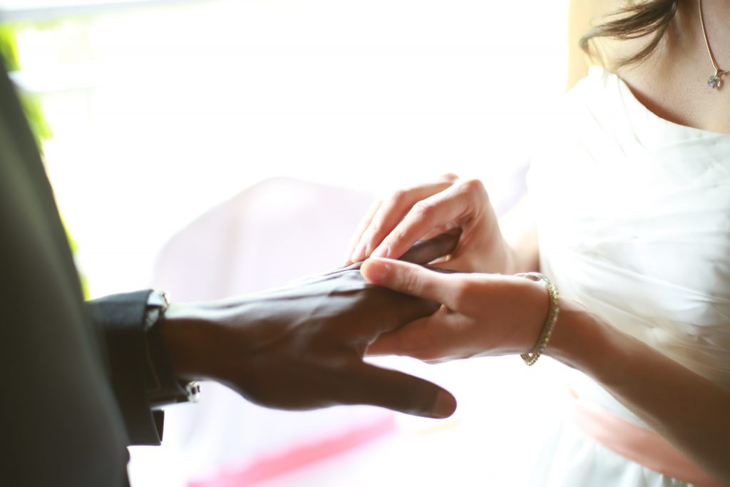 A woman putting a wedding ring on her partner.