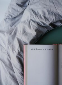 A notebook open on a bed with the title 'a little space to  be creative'