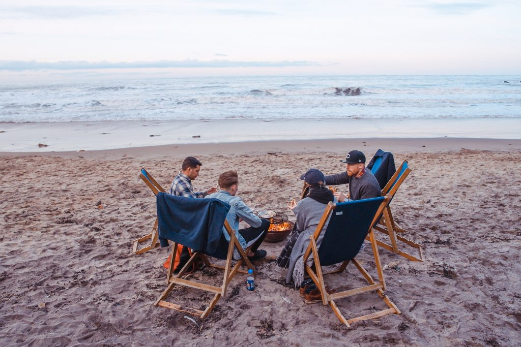 Four people are sat in deckchairs on a British beach with the sun just beginning to set behind the sea. They have a fire pit in the middle and blankets to keep them cosy.