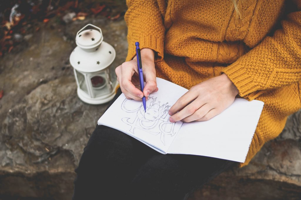 A close-up of a person's lap, sitting on a stone with a white lantern next to them. They are wearing a mustard yellow jumper and sketching a pencil outline of a girl in a notebook.