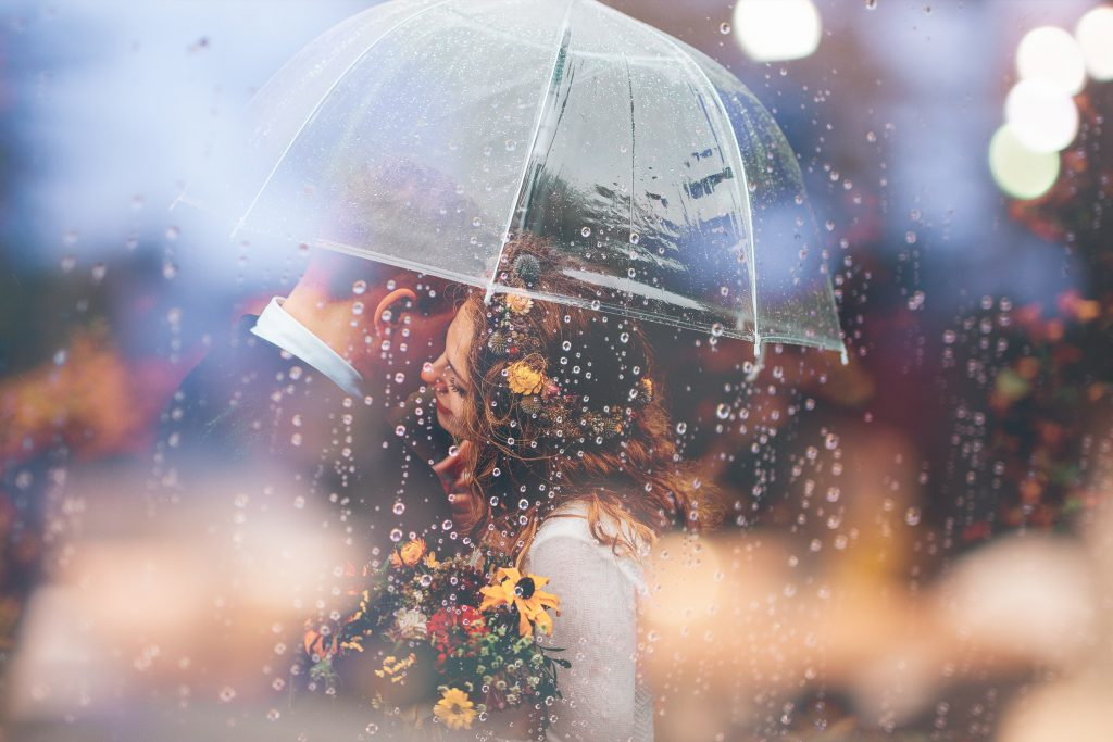 A couple, just married, kissing under a clear umbrella with rain falling all around them. Rain is one of those wedding superstitions that is good luck instead of bad!
