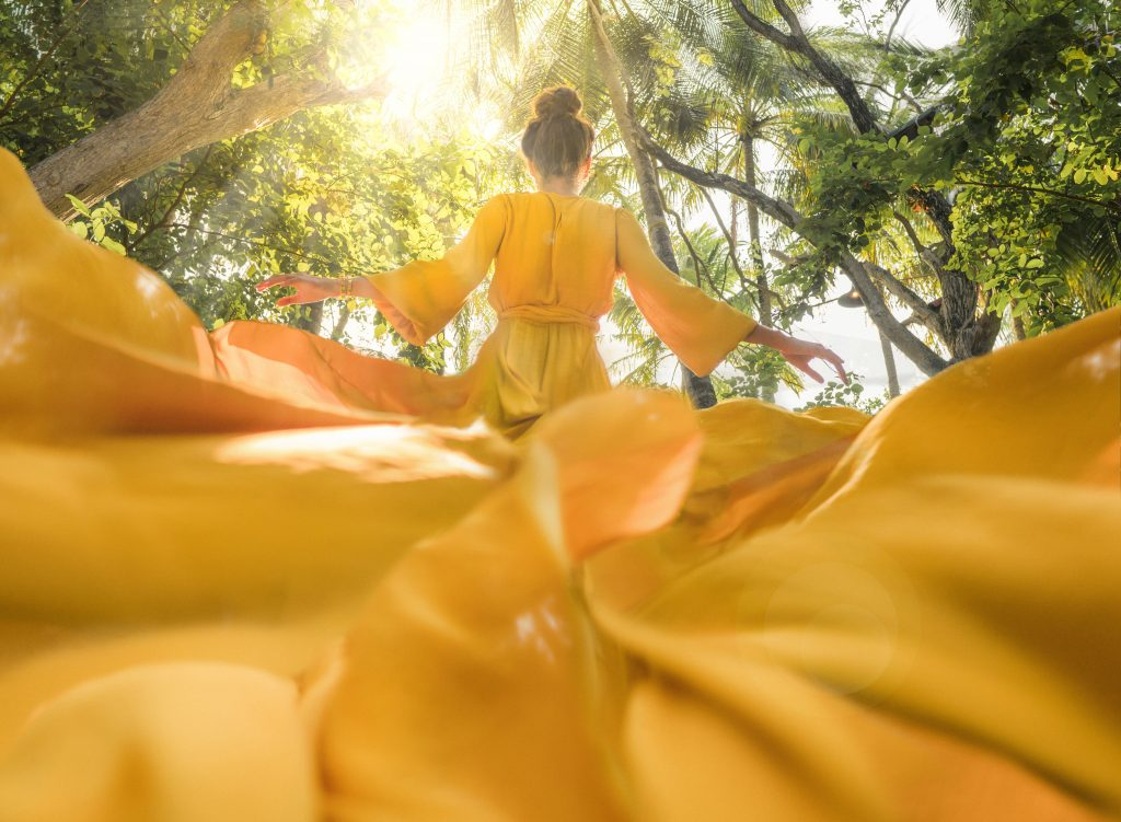 A person stands in a forest with her back to the camera wearing a yellow dress. The dress is flowing out and filling the bottom half of the camera frame.