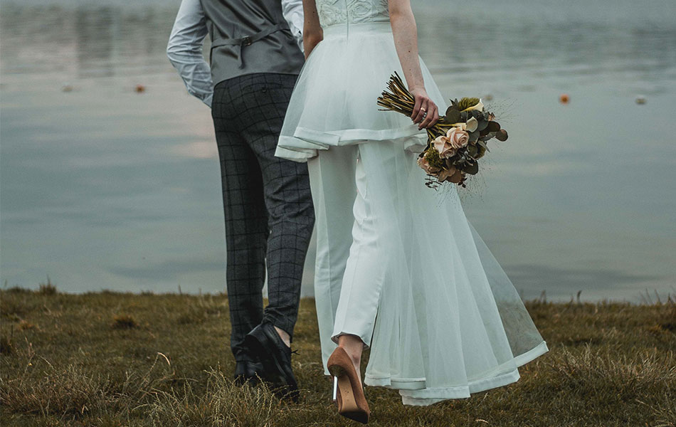 A bride wearing a short wedding dress with trousers underneath. Choosing separates you can wear again is great for couples who want to have a minimalist wedding.