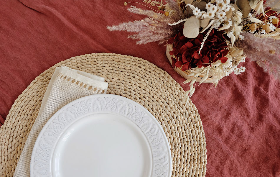 Embrace minimalist weddings by choosing dried flowers like these white and red ones on a rust coloured tablecloth with rattan place mat.