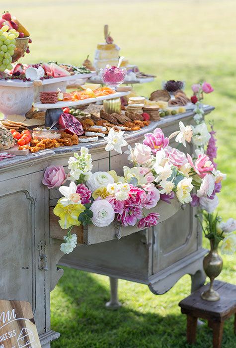 A dresser is filled with flowers spilling out of the drawer and covered in food for grazing to reduce wedding food waste