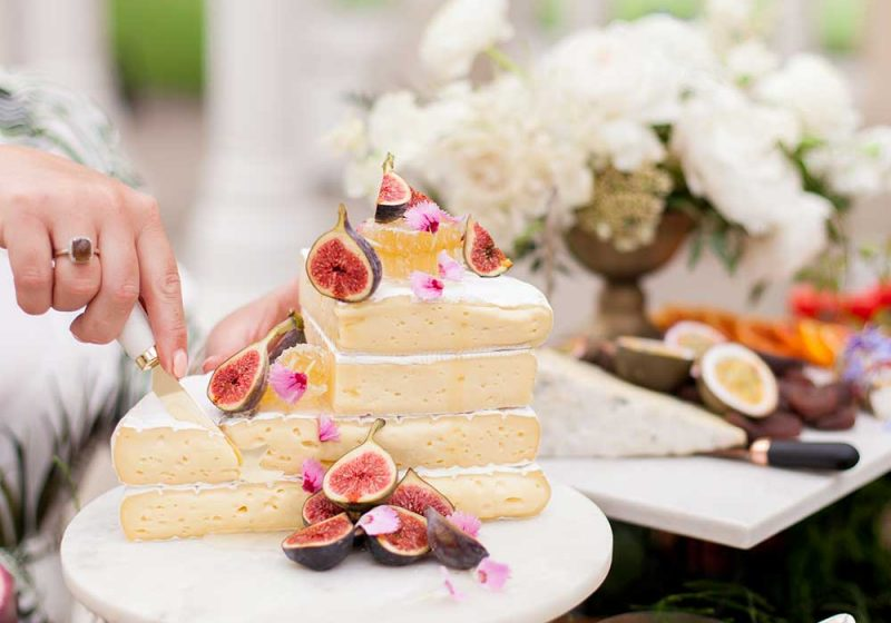 A hand cuts a tower of cheese covered in figs and orange segments.