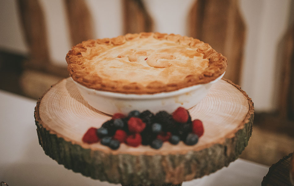 Have a minimalist wedding by swapping out cake for dessert, like this tier of three sweet pies on wooden log slices decorated with fairy lights.