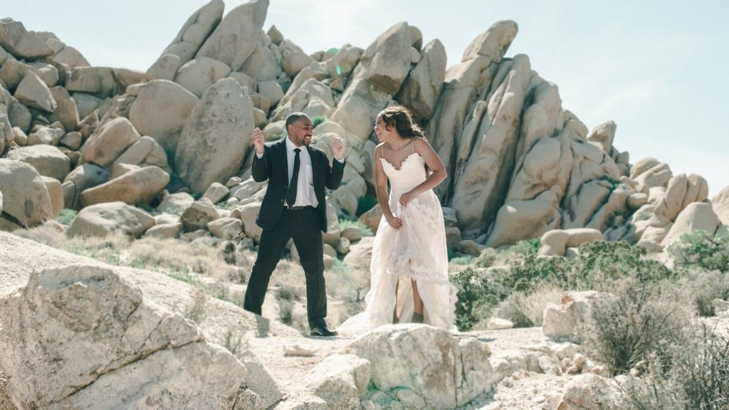 A married couple avoiding wedding planning stress by taking time out on their wedding day. They stand in their wedding dress and suit on some rocks being silly and having fun together.