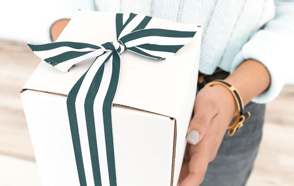 A package of leftovers to reduce wedding food waste, wrapped in a striped ribbon