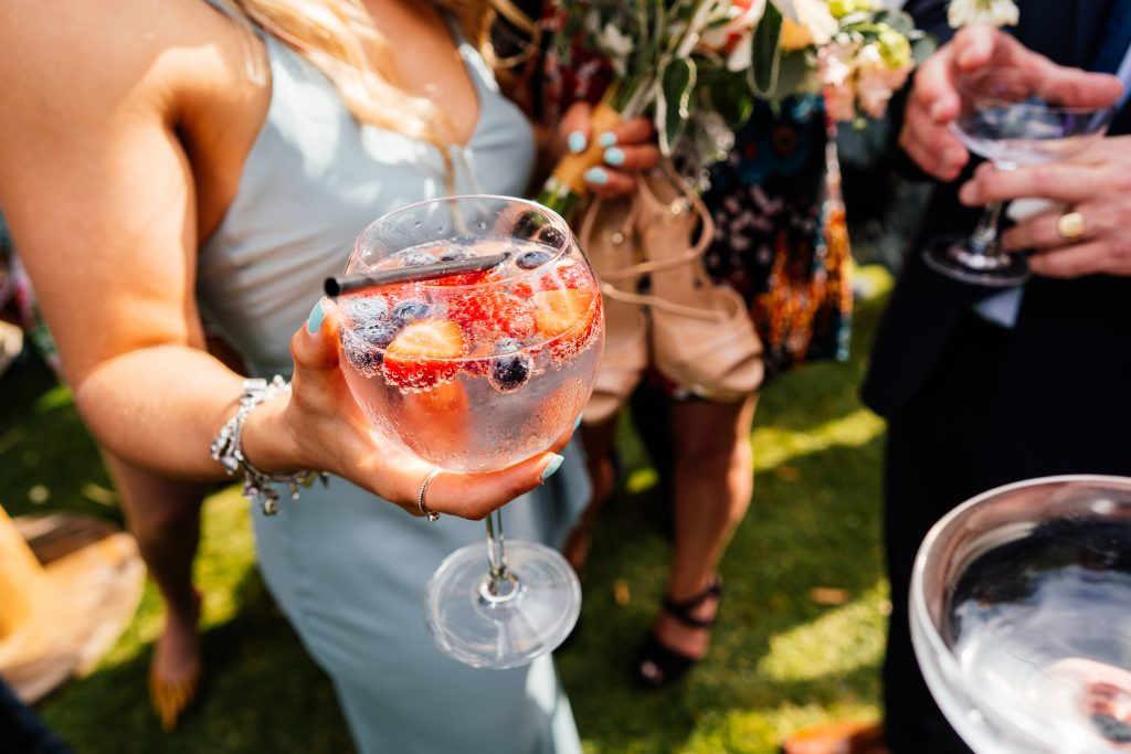 A glass of a gin cocktail held by a bridesmaid at a summer wedding.