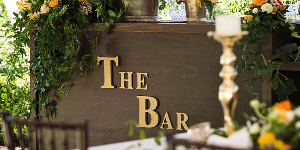 Wedding bar covered in bright flowers and foliage