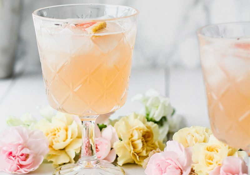 A peach coloured cocktail and small spray roses