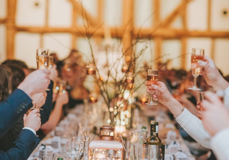 Guests raising their glasses of fizz in a toast during a joint wedding speech