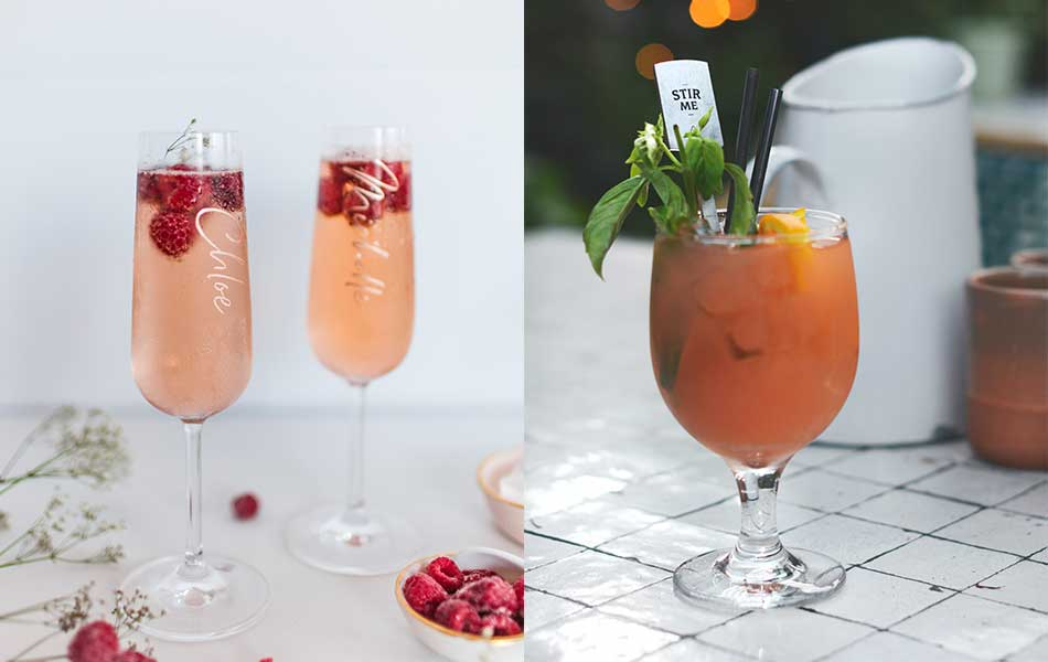 The left image shows two champagne glasses filled with pink champagne and raspberries with names written on each glass. The right image shows a glass of tomato juice with mint and a paper stirrer which reads 'stir me'. Both are examples of table plan ideas for your wedding bar.