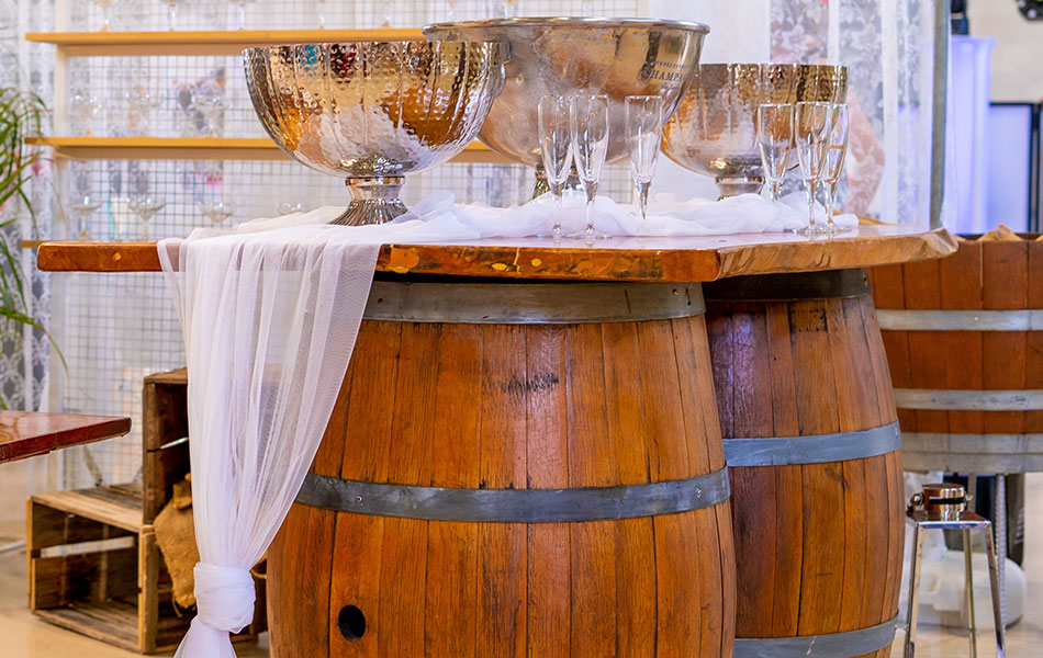 A wedding bar wine bar with two large barrels and an oak top holding champagne glasses.