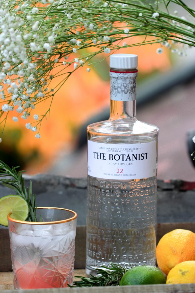 A botanical wedding bar with a bottle of The Botanist gin, lemons, limes and a glass of gin and tonic with a sprig of rosemary.