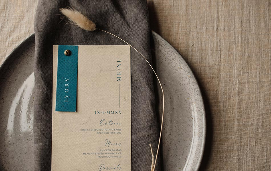 Eco-friendly stationery, cream menu card and blue place card sitting on a grey napkin with a dried bunny tail.