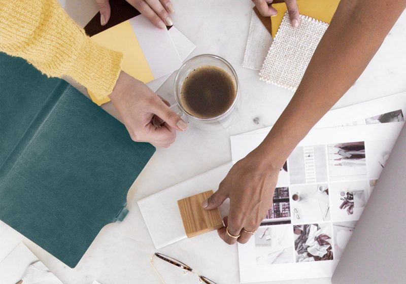 A flatlay of eco-friendly stationery and colour swatches with two people reviewing the items whilst holding a cup of coffee