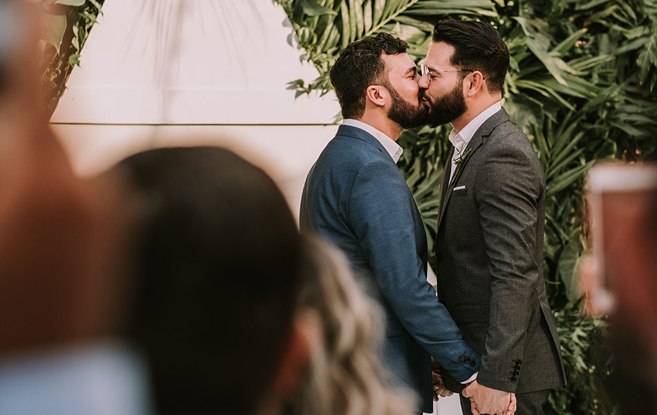 A gay couple kissing during a wedding ceremony where they have written their own wedding vows