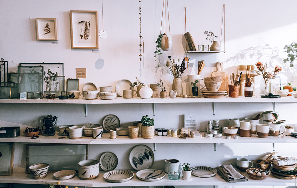 A thrift/charity shop with rows of earthy plates and mugs