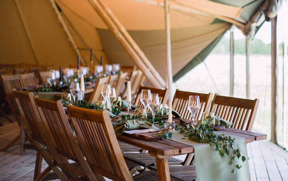 A wooden table and chairs set-up in a tipi with  a green runner and foliage