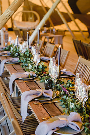 A considerate wedding table styled with purple napkins and candles and a greenery runner